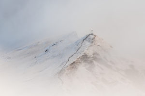 The summit cross of the Ladizköpfle (1921m) in the Karwendel near the Falkenhütte at the beginning of winter with clouds, fog and snow