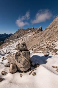 Ein Steinmandl als Wegmarkierung beim Aufstieg zur Lalidererspitze im Akrwendel. Im Hintergrund die Ladiztürme und die Sonnenspitze.
