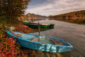 Blue fishing boat lies on the banks of Lake Walchen in autumn with autumn leaves.