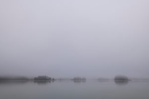 The islands of the Fohnsee in autumn. Fog creates a gray mood before sunrise.