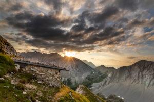 Sonnenaufgang im Karwendel über der Stempeljochspitze mit Biwakhütte im Vordergrund und Rumerspitze auf der rechten Seite.
