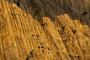 Morgendliches Sonnenlicht trifft auf die harten Strukturen und Risse im Fels des Karwendels der Nordkette in der Nähe der Pfeishütte