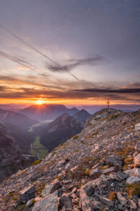 Sunrise over the Achensee behind the summit cross of the Sonnjoch in the Karwendel.