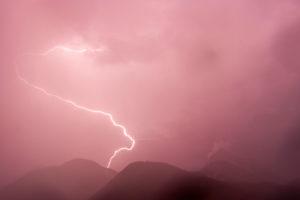 Blitzeinschlag während einem starken Sommergewitter in den Wildsteinkopf bei Mittenwald in den bayrischen Alpen, im Hintergrund Schemenhaft der Wetterstein