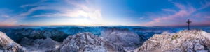 Morgenrot mit einer kleinen roten Sonne in der Ferne und dem Gipfelkreuz der Birkkarspitze im Karwendel.