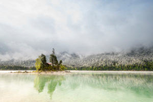 A small lonely island with a log cabin and red roof, in the middle of the beautiful Eibsee below the Zugspitze in the Bavarian Alps of the Wetterstein Mountains during the Eisheiligen - fresh snow in the background on the forest and cloud mood.