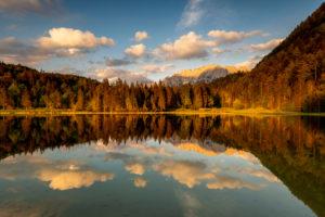 Abendlicht bei leichten Wolken am Ferchensee, oberhalb von Mittenwald. Der Waldrand und das im Hintergrund liegende Karwendel wird warm angeleuchtet und spiegelt sich im klaren Wasser des See.
