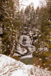 Waterfall of the Obernach Canal between Wallgau and the Walchensee in the Bavarian Prealps in winter with snow