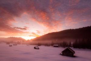 Sonnenaufgang in den bayrischen Alpen nahe Garmisch-Partenkirchen. Im Hintergrund die Soierngruppe des Karwendel und phantastische Farben, im Vordergrund klassische Heuschober und Morgennebel, bei Schnee und Kälte.