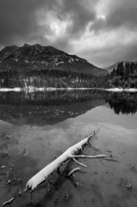 Winter at the Krün reservoir in the early morning, with clouds and snow