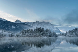 Sunrise at the winter reservoir Krün after nightly fresh snow and in the background the Karwendel mountains