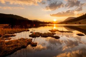 Sonnenuntergang im Frühling am Geroldsee am Ufer mit Schilfinsel bei Wolken