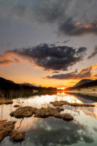 Spring sunset at Geroldsee on the shore with reed island with clouds