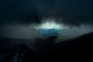 Storm over the Isar valley. Severe weather with the summit cross / mountain peak of the Martinkopf, just below the Herzogstand in the Ester Mountains, the Bavarian Prealps. A dark, heavy storm cloud and rain only allow a small viewing window to Mittenwald, Wallgau and the Wetterstein Mountains.