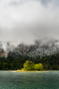 Kleine grüne Insel im Eibsee, unterhalb der Zugspitze in den bayrischen Alpen des Wettersteingebirge während den Eisheiligen im Frühling. Im Hintergrund Schnee auf dem frischen Grün des Waldes und dichte Regenwolken.