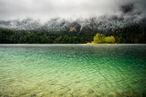 Small green island in the Eibsee, below the Zugspitze in the Bavarian Alps of the Wetterstein Mountains during the ice saints in spring. In the background snow on the fresh green of the forest and thick rain clouds.