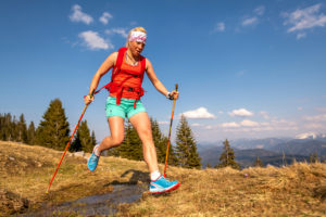Trail runner jumps over a small stream on a mountain meadow, in the background the German Alps and blue sky.