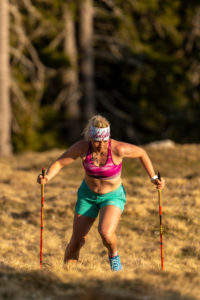 Concentrated trail runner with a natural figure while mountain running on Simetsberg on spring meadow