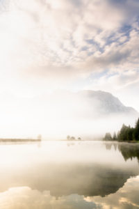 Autumn mood at a small lake in the Bavarian Alps, in the background the Karwendel Mountains, a small peninsula in the fog and the reflection in the water. The foggy atmosphere with the rugged mountains has an almost mystical effect.
