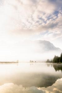 Herbststimmung an einem kleinen See in den bayrischen Alpen, im Hintergrund das Karwendel Gebirge, eine kleine Halbinsel im Nebel und die Spiegelung im Wasser. Fast mystisch wirkt die Nebelstimmung mit dem schroffen Gebirge.