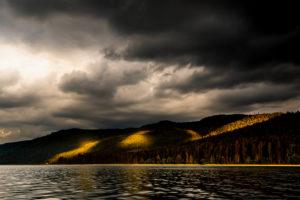 Unwetter Wolken und Lichtstimmung über Altlach, am Walchensee in den bayrischen Voralpen dem Karwendel und Estergebirge. intesives Sonnenlicht erleuchtet Abschnitte des Waldes, während dunkle Sturmwolken, den rest abschatten.