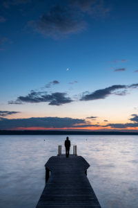 A single man in a hoodie stands on a wooden jetty on the banks of the Ammersee during sunset with a crescent moon.