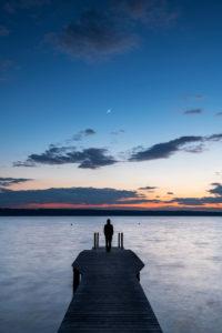Ein einzelner Mann mit Kapuzenpullover steht auf einem Holzsteg am Ufer des Ammersee während Sonnenuntergang mit Sichelmond.