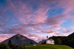 Das kleine Annakircherl, eine kleine Kapelle auf einem Hügel in Achenkirch am Rend des Karwendel inden Alpen, Tirol nach Sonnenuntergang. Lila und Blautöne dominieren den Abendhimmel. Im Hintergrund die Berge.