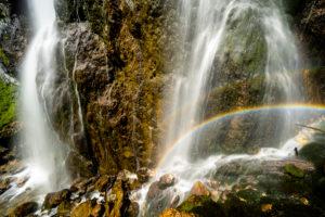 Regenbogen am Dalfazer Wasserfall unterhalb des Dalfazer Klettersteiges am Achensee im Rofan Gebirge. Wasser stürzt an der Felswand hinab und bildet im Sonnenschein einen wunderbaren kleinen doppelten Regenbogen.