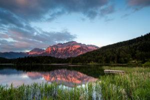 Der Lautersee bei Mittenwald spiegelt das Alpenglühen des Karwendel, mit Schilf und Steg im Vordergrund.