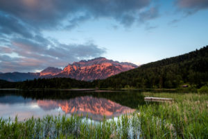 The Lautersee near Mittenwald reflects the alpine glow of the Karwendel, with reeds and a footbridge in the foreground.