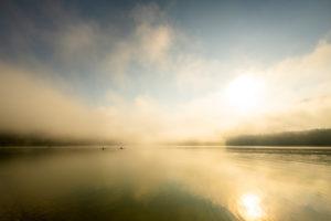 Kayakfahrer bzw. Renn-Skiff fahrer mit speziellen Wettkampfbooten genießen am frühen Morgen während Sonnenaufgang eine Fahrt am Sylvensteinspeicher, während Nebel und Lichtstimmung.