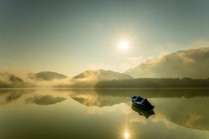 A single rowing boat with tarpaulin is moored at the Sylvensteinspeicher lake, while the sun sends its rays over the lake with light fog in the early morning and is reflected in the water.