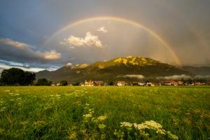 regenbogen über der bayrischen Ortschaft Krün in den Alpen. Im Hintergrund die von der Abendsonne beleuchteten Schöttelspitze und Soierngruppe im Karwendel Vorgebirge.