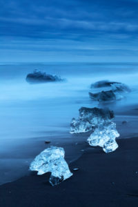 Diamond Beach, pieces of ice   on the beach with icebergs in the background