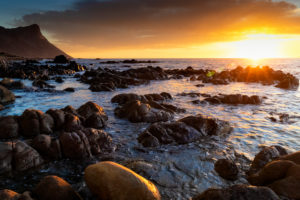 Sunset at False Bay (South Africa) with clouds and boulders on the foreground, Western Cape, South Africa