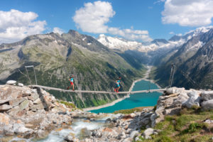 two runners on the tibetan bridge near Olperer hut with Schlegeis Stausee on the background, Zillertal Alps, Tyrol, Schwaz district, Austria.