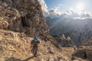A hiker on the Bepi Zac High Trail passing close to a war cave, Costabella Ridge, Marmolada group, Dolomites, Fassa Valley, Trento province, Trentino-Alto Adige, Italy