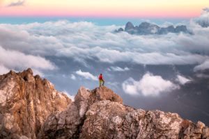Lonely man stands on top of a mountain ridge, on the background a sea of clouds around the Agner mountain range, Pale di San Martino group, view from Costabella ridge, Dolomites, Italy