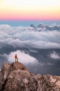 Einsamer Mann steht auf einem Gebirgsrücken, im  Hintergrund ein Wolkenmeer um den Agner-Gebirgszug, Gruppe Pale di San Martino, Blick vom Costabella-Kamm, Dolomiten, Italien