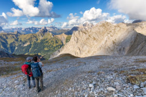 Two hikers observe Sella group and Marmolada group from the Bepi Zac High Trail, Costabella Ridge, Marmolada group, Dolomites, Fassa Valley, Trento province, Trentino-Alto Adige, Italy