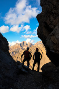 Two hikers looking the Gran Vernel group in a small fork along the Bepi Zac High Trail, Costabella Ridge, Marmolada group, Dolomites, Fassa Valley, Trento province, Trentino-Alto Adige, Italy