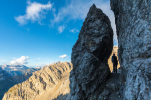 A hiker at the narrowest point of the Bepi Zac High Trail, Costabella Ridge, Marmolada group, Dolomites, Fassa Valley, Trento province, Trentino-Alto Adige, Italy
