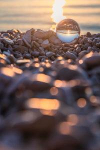 Kristallkugel am Kiesstrand von Mošćenička Draga bei Sonnenaufgang, Gespanschaft Primorje-Gorski Kotar, Kroatien