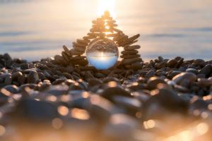 Stapel von pyramidenförmigen Kieselsteinen mit Kristallkugel am Strand von Mošćenička Draga bei Sonnenaufgang, Gespanschaft Primorje-Gorski Kotar, Kroatien