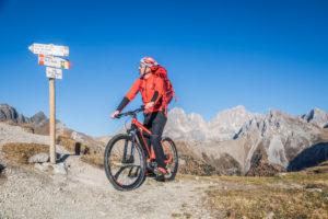 Ein Mann mit ebike MTB auf einem Weg im San Nicolò-Tal mit Marmolada im Hintergrund, Trentino, Dolomiten, Italien