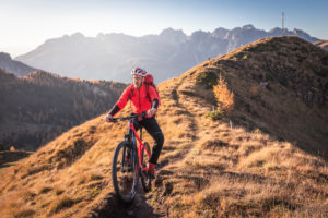 A man rides an ebike MTB on the tracks in the San Nicolò valley, Fassa valley, Trentino, Dolomites, Italy