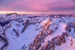 aerial view of dolomites mountains at sunrise with sasso vernale, cima uomo, marmolada group, on the horizon the pale di san martino and the lagorai mountain range, italy