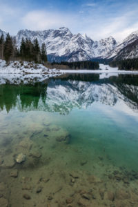 The upper lake of Fusine with mount Mangart on the background in winter. Fusine Lakes Natural Park, Fusine di Valromana, Tarvisio, Udine province, Friuli Venezia Giulia, Italy