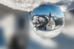 The parish churc of Rina di Marebbe - Welschellen seen through a crystal ball, municipality of Marebbe / Enneberg, Bolzano, Alto Adige, Südtirol, Italy